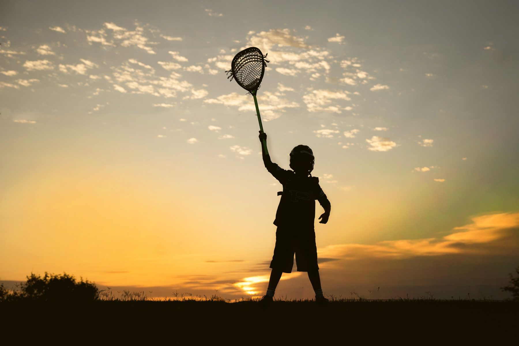 Boy holding up lacrosse stick in silhouette
