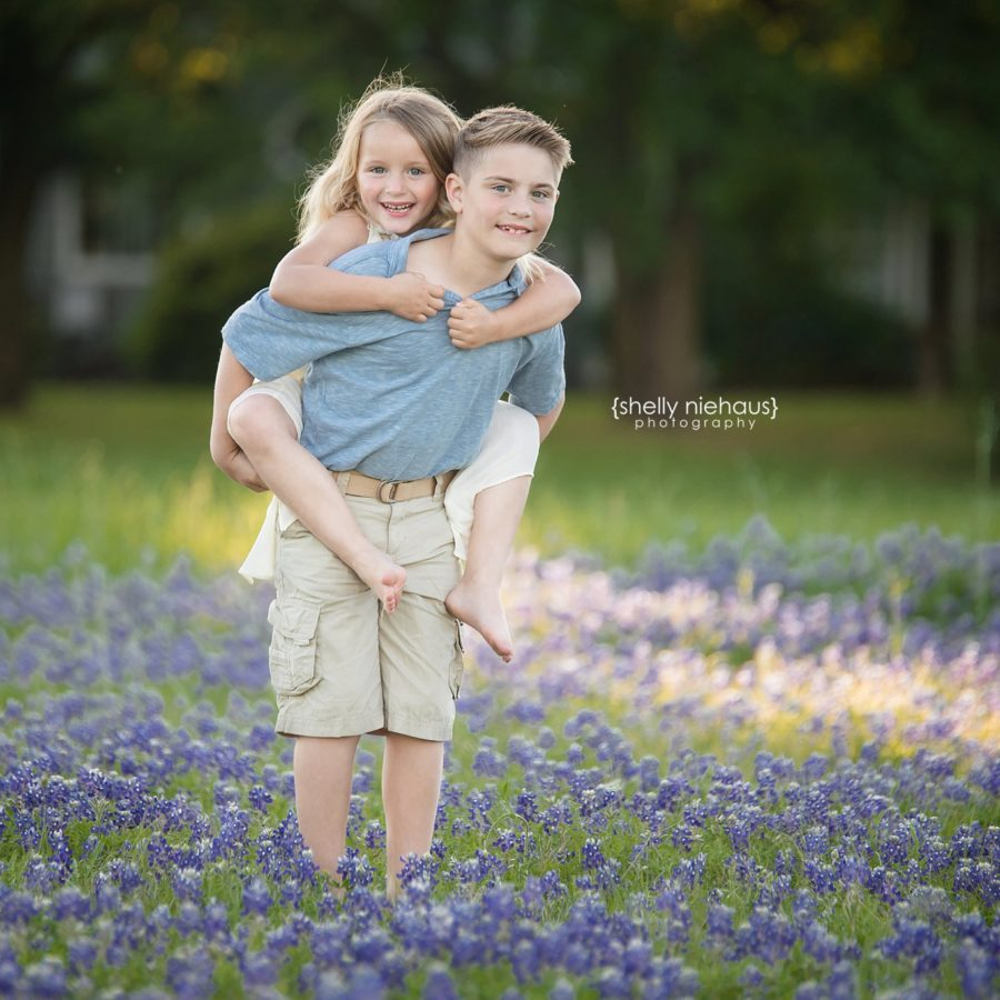 brother and sister piggy back ride in bluebonnets