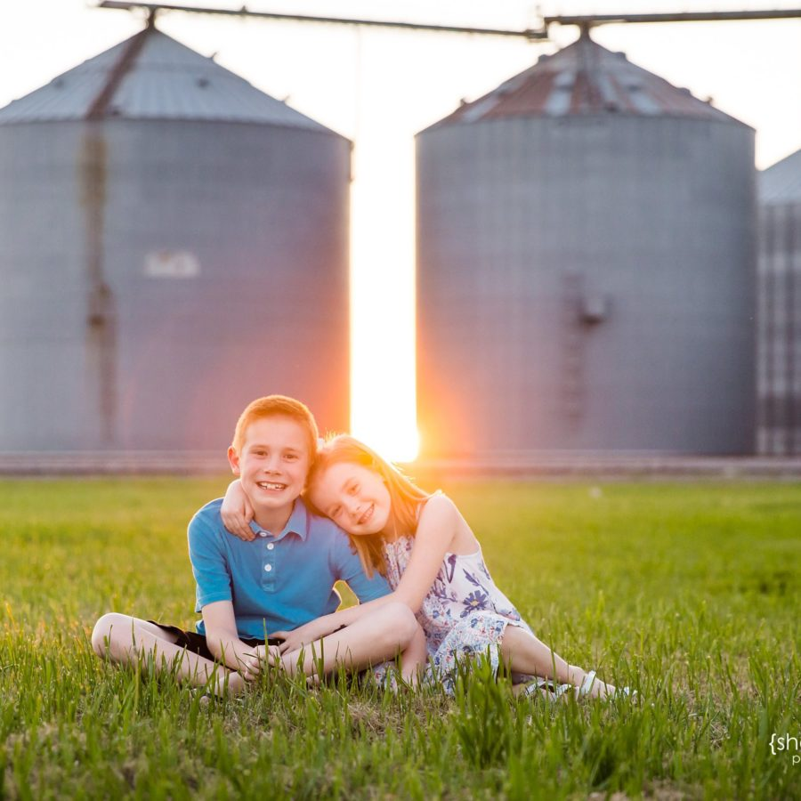 brother and sister hugging in front of silos at sunset - prosper tx photographer