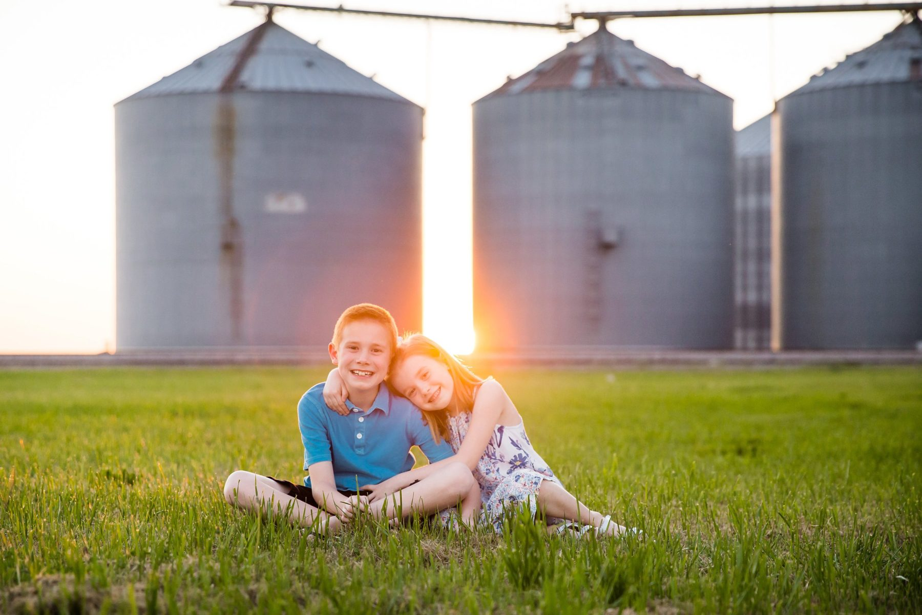 brother and sister in front of silos at sunset