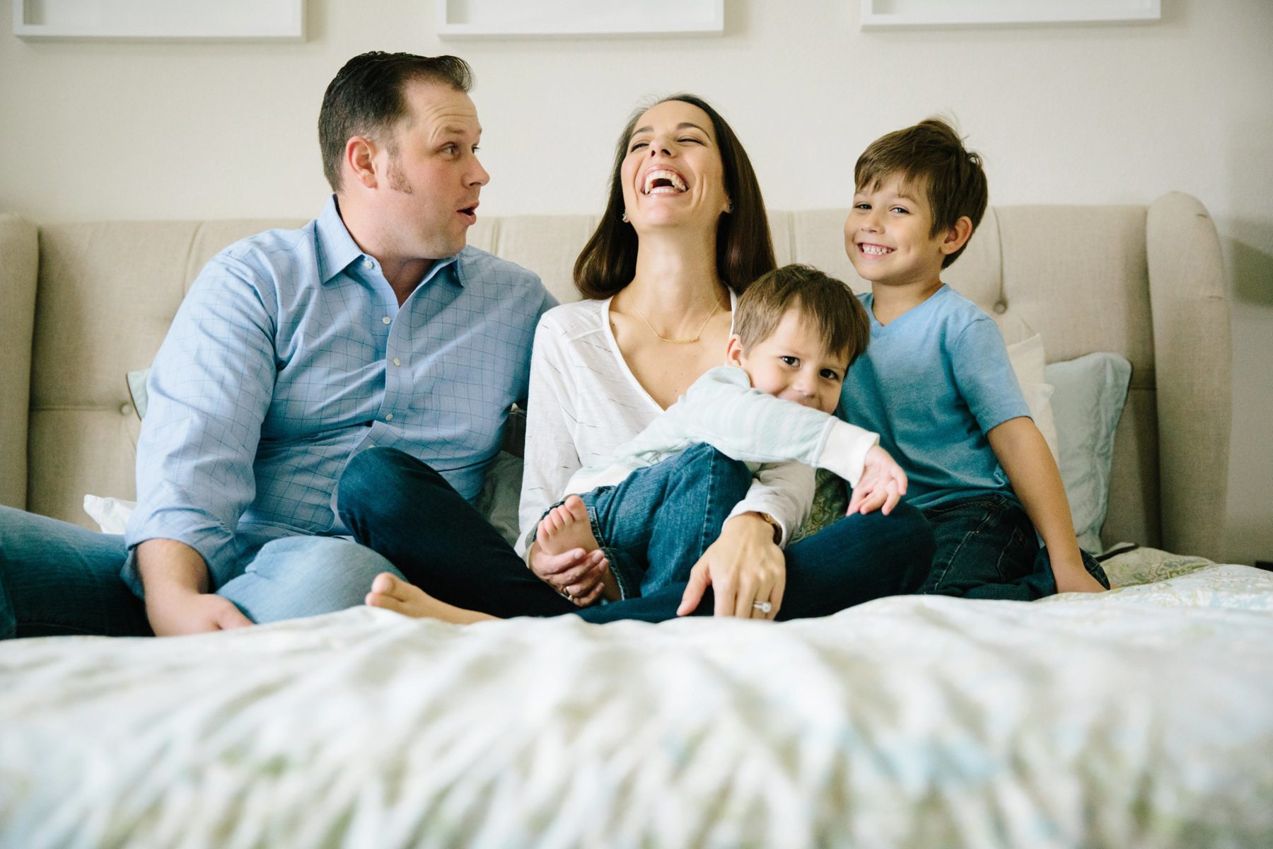 mom, dad and little brothers laughing on bed