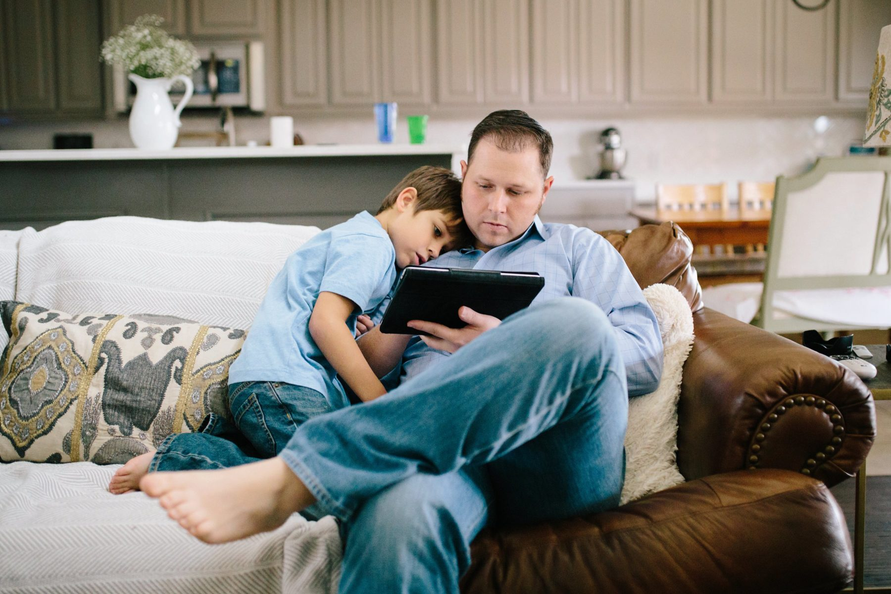 dad and son reading on couch - frisco tx