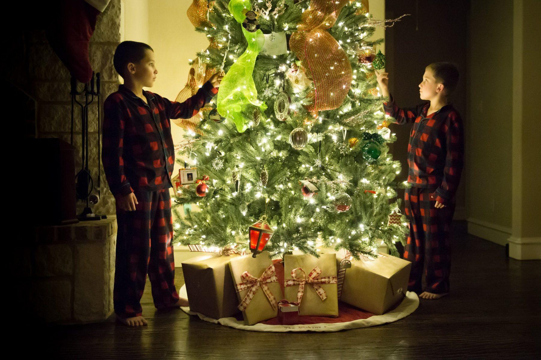Boys in Christmas PJs around tree