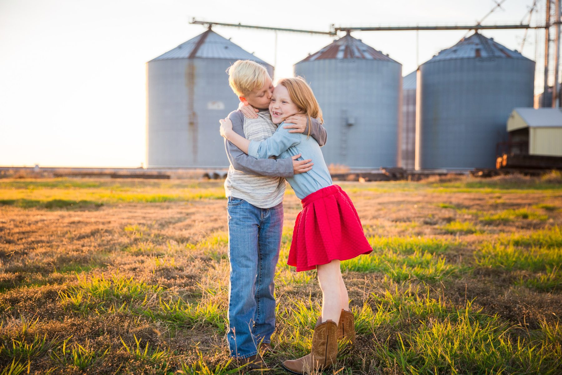 Brother and sister hugging in front of silos {Family Photographer| Prosper, TX}